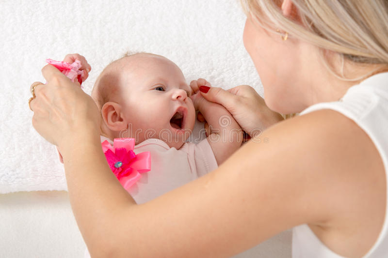 Mom is looking at a two-month girl with an open mouth. A two-month baby lying on his back on the bed, sitting next to the child and mother looking at her royalty free stock photography