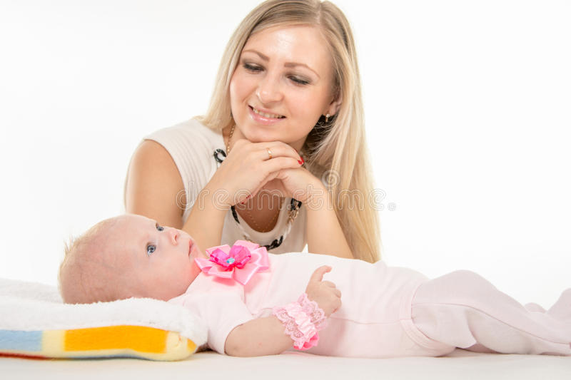 Mom looks at lying on the bed his two-year daughter. A two-month baby lying on his back on the bed, sitting next to the child and mother looking at her stock photos