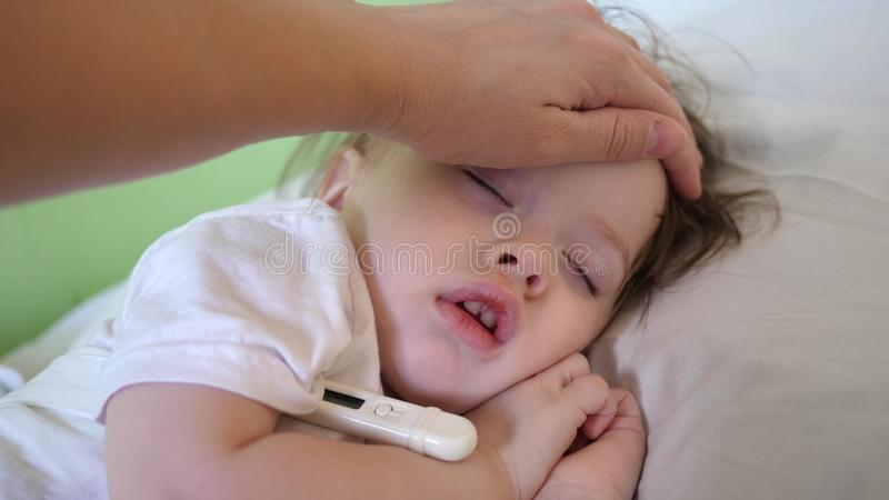 Mom measures temperature with thermometer to baby and caresses child with hand. close-up. baby sleeps in hospital ward. On white bed stock images