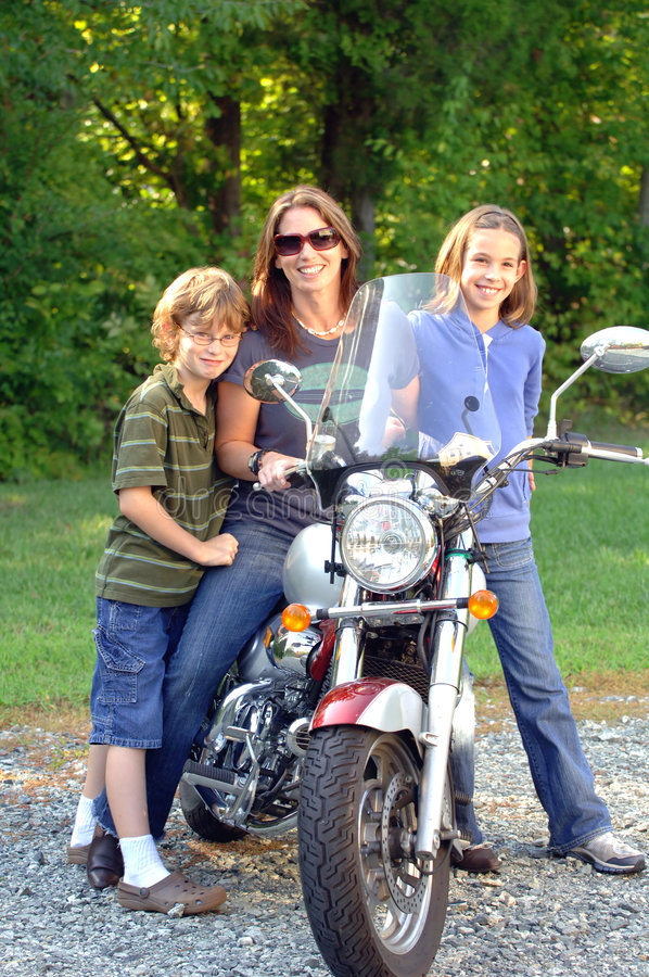 Mom with motorcycle and kids. A mom sitting on her motorcycle with her daughter and son next to her royalty free stock photos