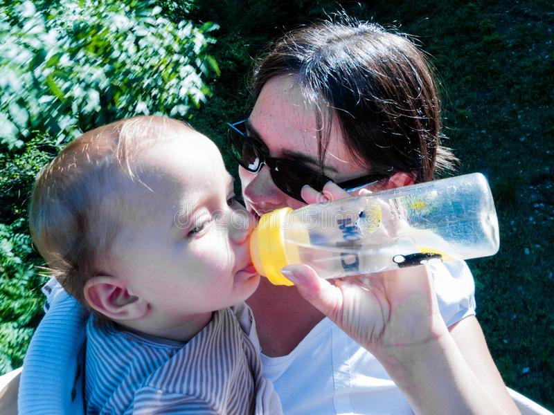Mom offers water to drink to her daughter, with a bottle stock photos