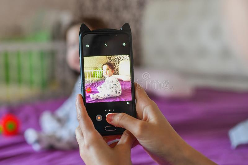 Mom photographs the child, as a keepsake. Mother photographer photographing of her baby on camera.  royalty free stock image