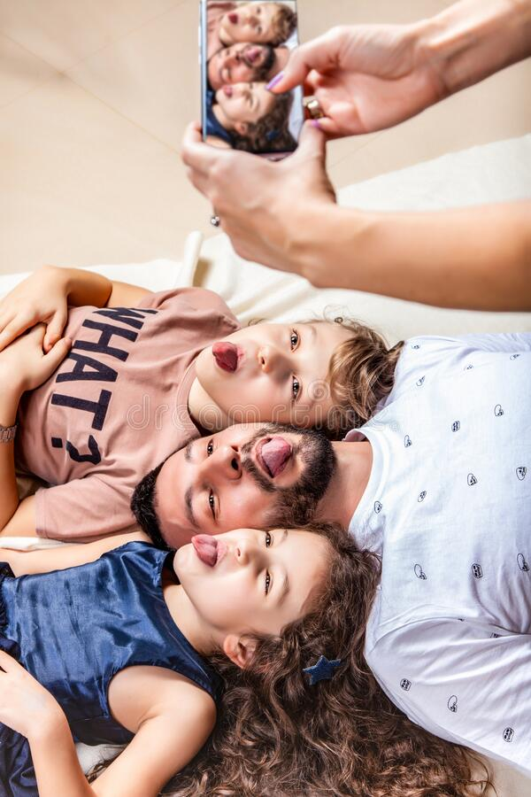 Mom photographs her family on a smartphone. Father lies in the middle between son and daughter, show tongue, family portrait stock images