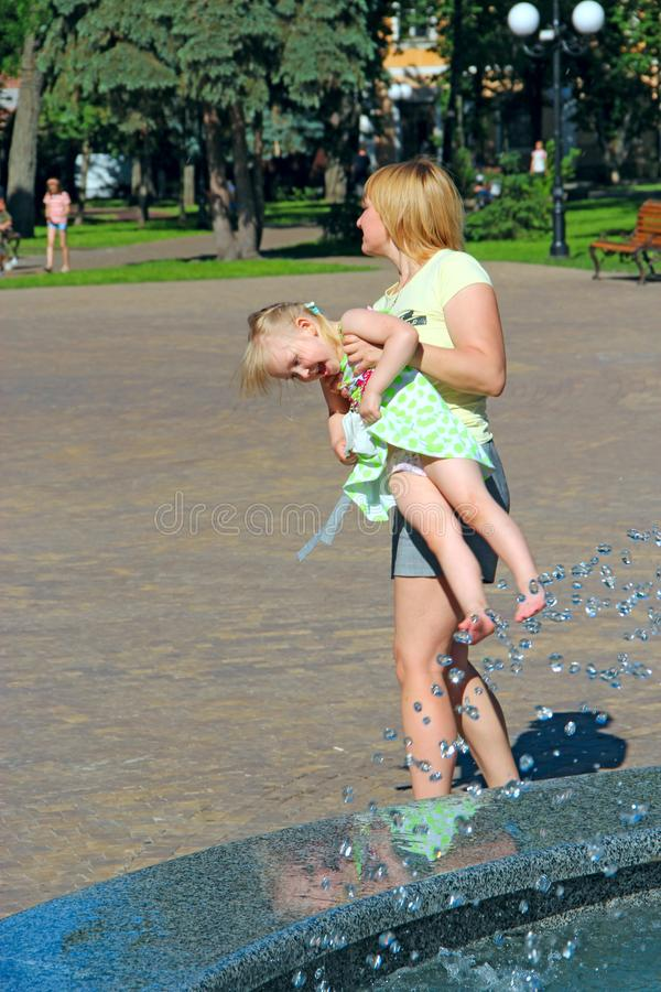 Mother carries naughty daughter in city. Parenting. Children emotions royalty free stock images