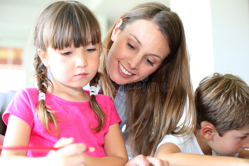 Mom playing with kids. Mother watching kids making drawings at home stock photos
