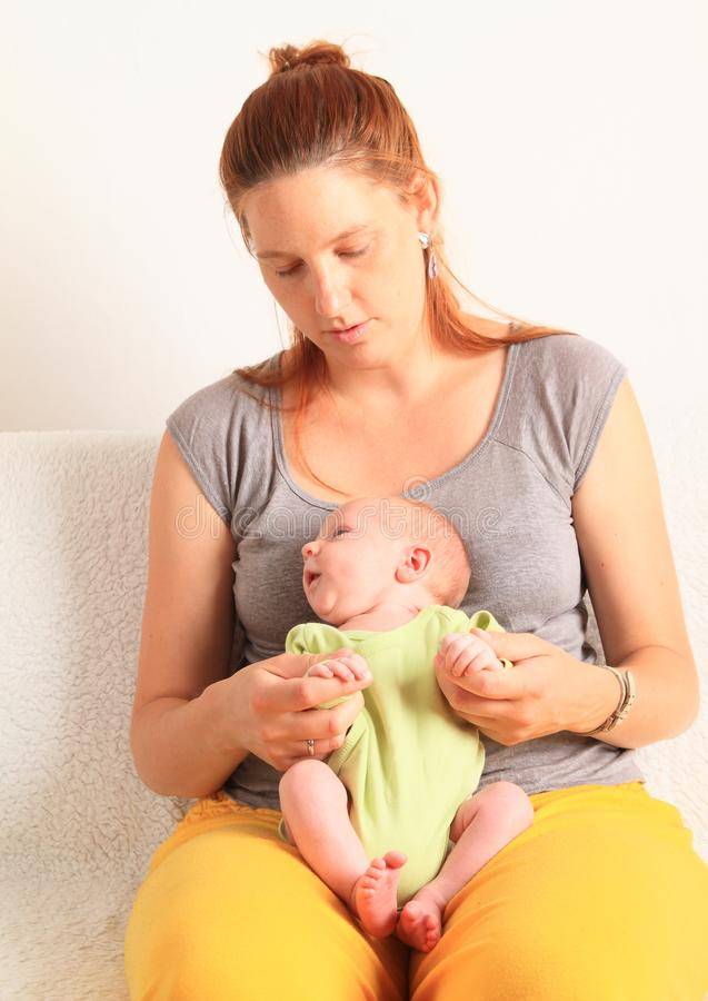 Mom playing with newborn baby boy on her lap stock photos