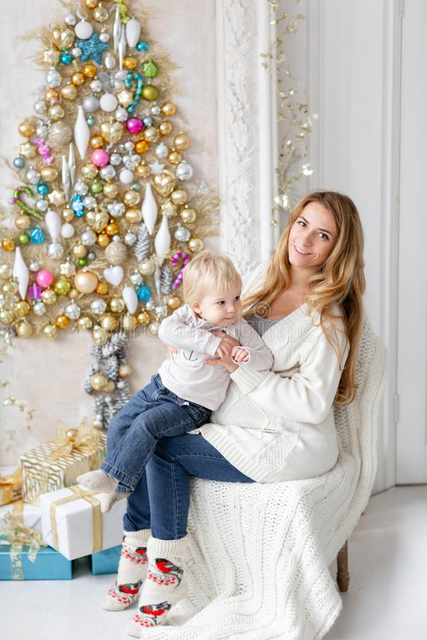 Mom plays with child. Happy family Portrait In Home - young pregnant mother embraces his little son. Happy new year stock photo