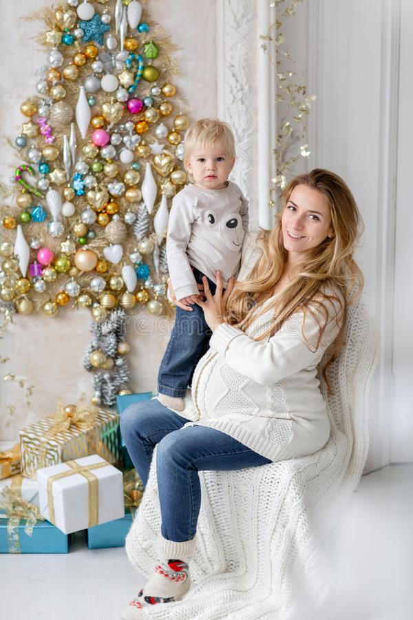Mom plays with child. Happy family Portrait In Home - young pregnant mother embraces his little son. Happy new year royalty free stock photo