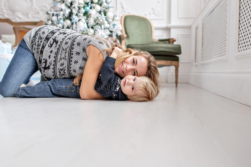 Mom plays with child. Lying on the floor Happy family Portrait In Home - young pregnant mother embraces his little son. Mom plays with child. Happy family royalty free stock images