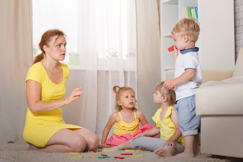 Mom plays with children twins. In the room, Mom scolds her son for a bad deed stock photo