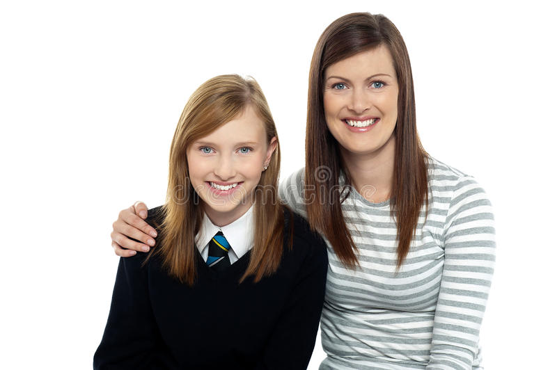 Mom posing with arms around her cute daughter stock images