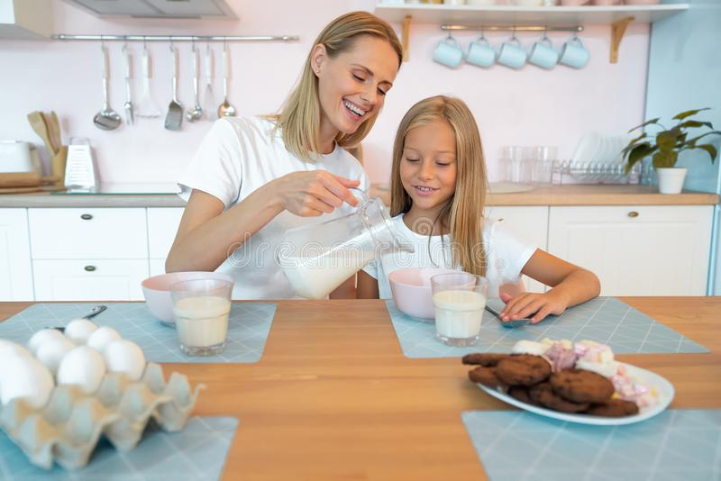 Mom pours milk to her daughter for breakfast with chocolate flakes. have a good time together, dressed alike.  royalty free stock photography