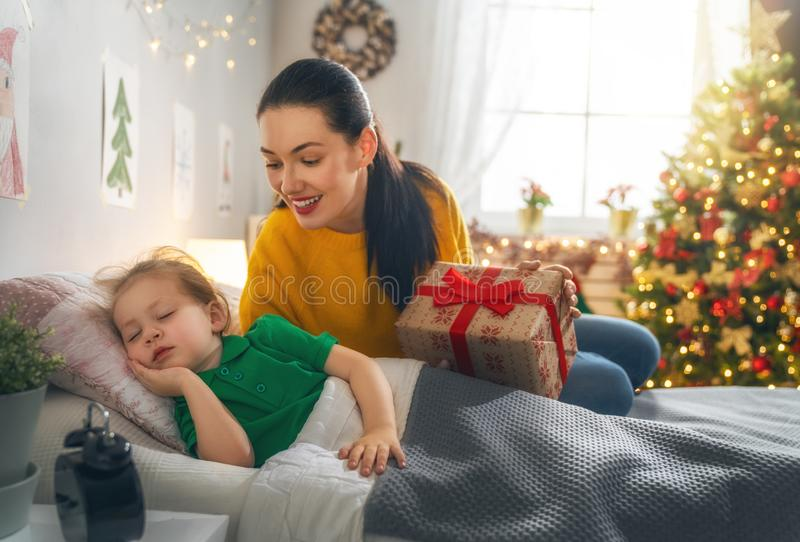 Mom preparing Cristmas gift to daughter royalty free stock photography