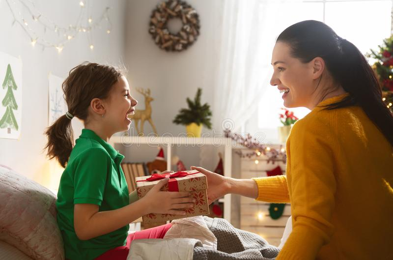Mom preparing Cristmas gift to daughter. Merry Christmas and Happy Holidays! Cheerful mom preparing gift to her cute daughter girl. Parent and little child near royalty free stock image