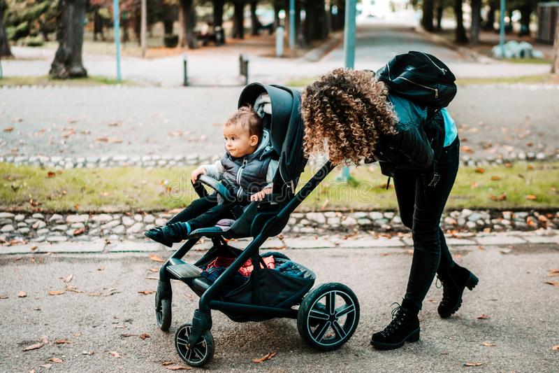 Happy mom pushing stroller and smiling, laughing. Young mother taking care of little son royalty free stock images