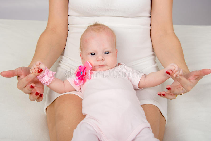 Mom put a two-month baby on her knees and holding his pen. A two-month baby lying on her back on her mother's lap and looking at her stock photography