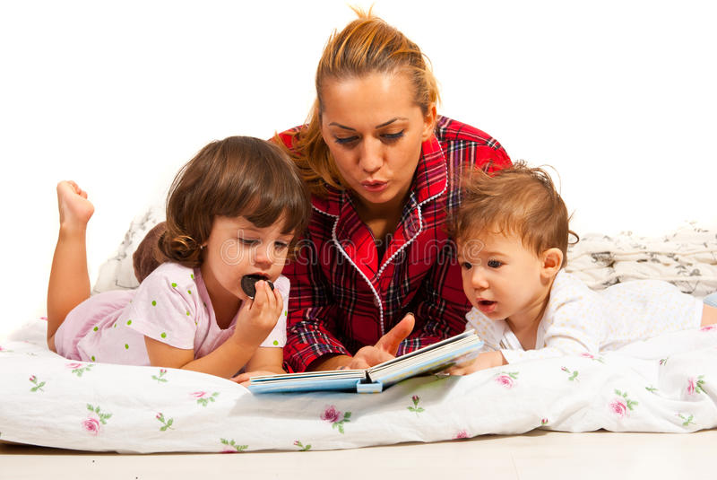 Mom reading bedtime story. Mother reading bedtime story to her children in bed stock photography