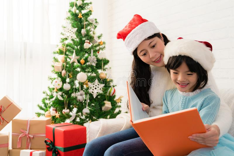 Mom reading a book to her cute daughter royalty free stock images