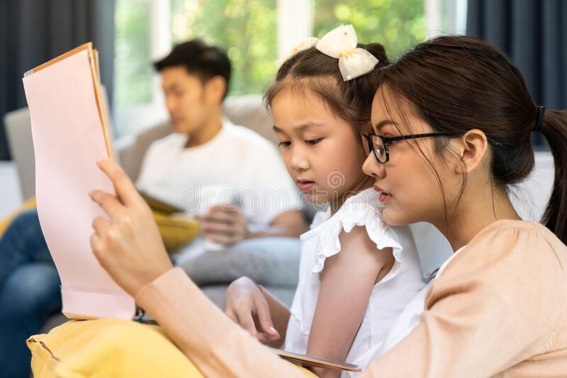 Mom reading story to daugther while dad work from home royalty free stock photo