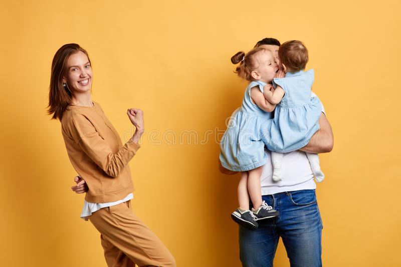 Mom rejoicing at her husband who playing and with noisy naughty children. Beautiful cheerful women rejoicing at her husband who playing and fooling aroundis royalty free stock images