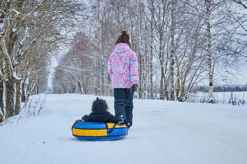 Mom rolls her little son on tubing in the Park in the winter. Happy family outdoors. winter fun for young children. Mom rolls her little son on tubing in the royalty free stock image