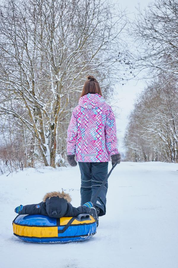 Mom rolls her little son on tubing in the Park in the winter. Happy family outdoors. winter fun for young children. Mom rolls her little son on tubing in the stock image