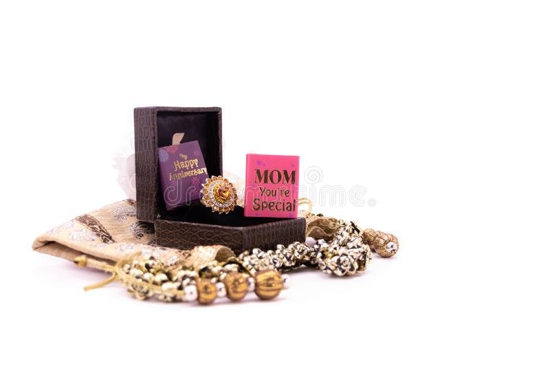 Mom`s anniversary concept. Golden ring in a lather gift box with handmade pouch and mom you`re special card on white background stock images