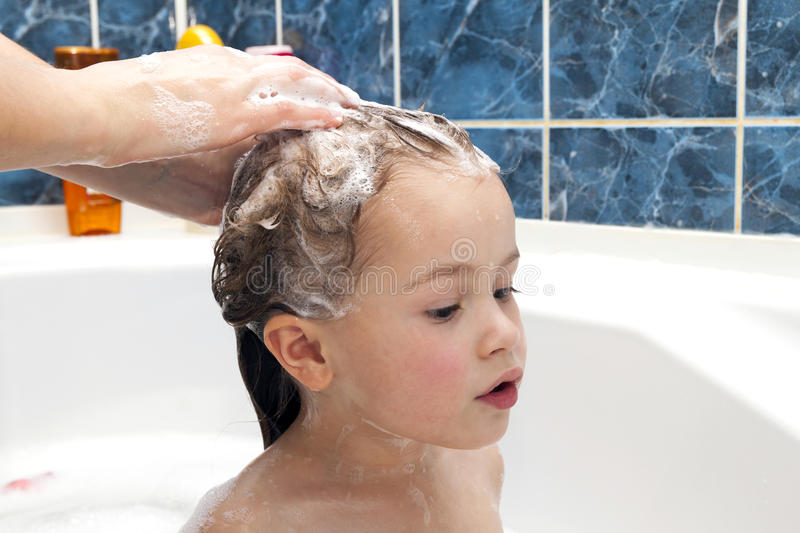 Mom`s hands washing little girly`s head in the bathroom. The sym stock image