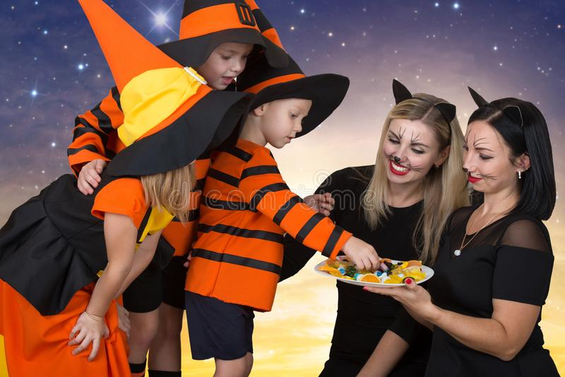 Happy company celebrates Halloween.Mom`s treat children with candy. Funny kids in carnival costumes royalty free stock photography