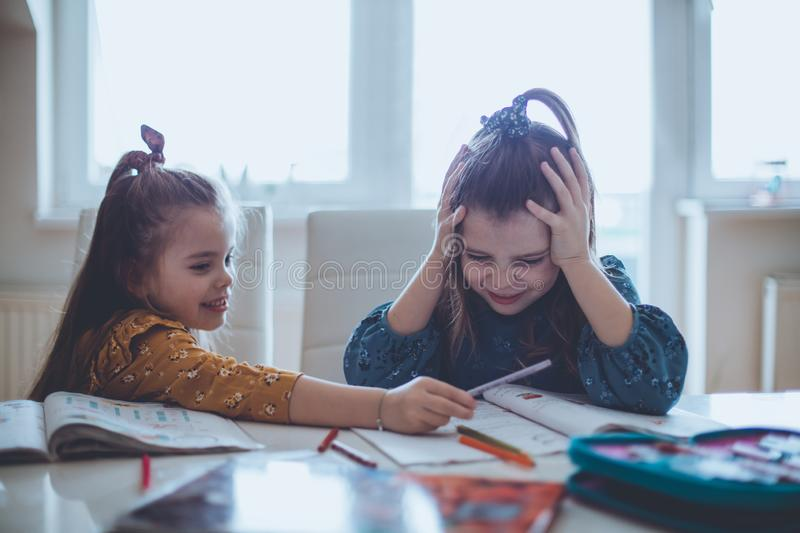 Mom said to repeat this task, it`s not good. Two little girls working homework at home. Space for copy stock photography