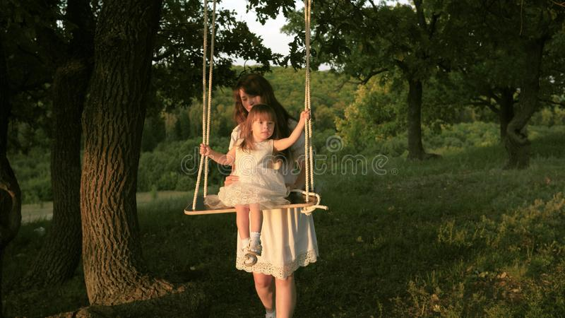 Mom shakes her daughter on swing under a tree in sun. close-up. mother and baby ride on a rope swing on an oak branch in royalty free stock photography