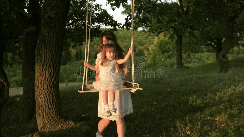 Mom shakes her daughter on swing under a tree in sun. close-up. mother and baby ride on a rope swing on an oak branch in royalty free stock photos