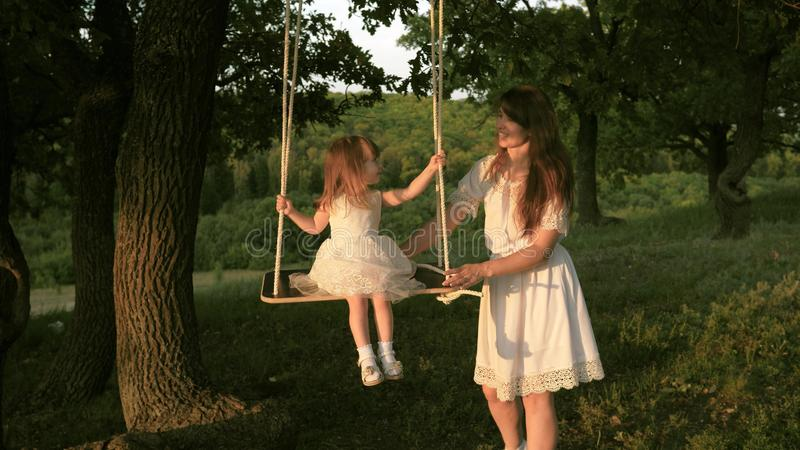 Mom shakes her daughter on swing under a tree in sun. close-up. mother and baby ride on a rope swing on an oak branch in royalty free stock image