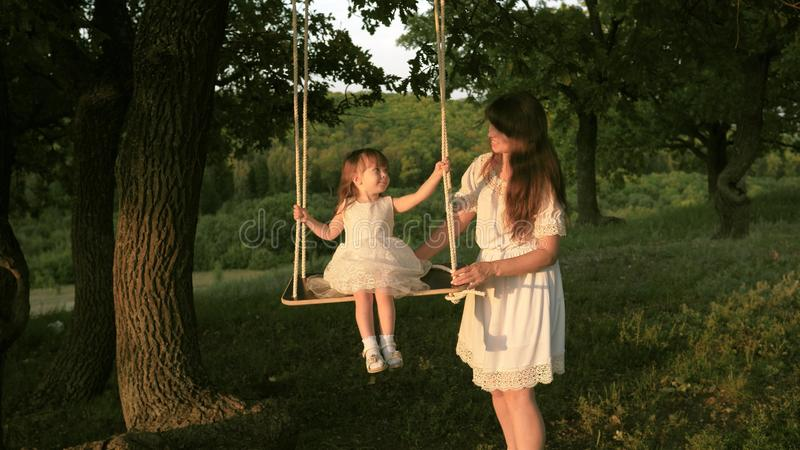 Mom shakes her daughter on swing under a tree in sun. close-up. mother and baby ride on a rope swing on an oak branch in stock images