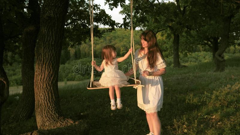Mom shakes her daughter on swing under a tree in sun. close-up. mother and baby ride on a rope swing on an oak branch in stock photos