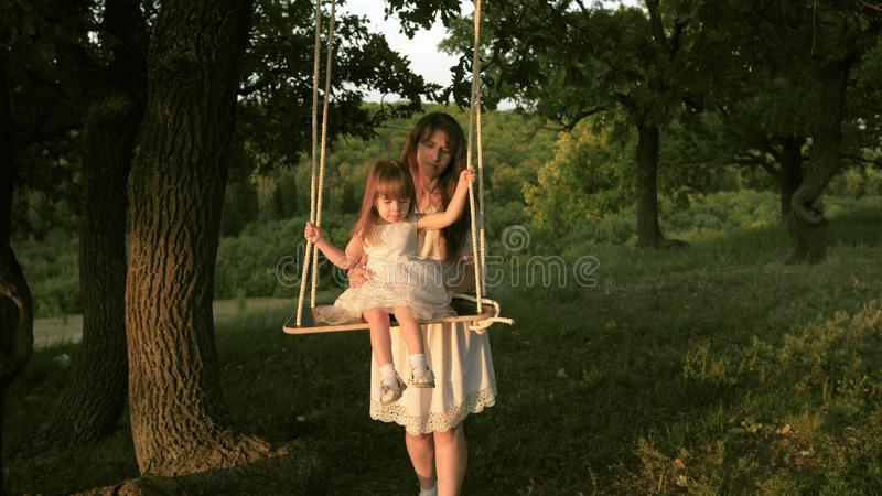Mom shakes her daughter on swing under a tree in sun. close-up. mother and baby ride on a rope swing on an oak branch in stock photography