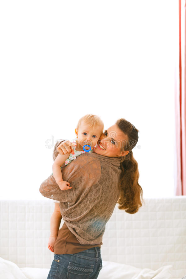 Mom showing baby something by pointing in camera stock photo