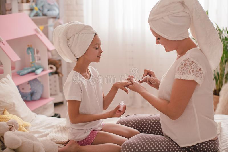 Mom shows her daughter how to do a manicure stock image