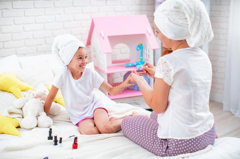 Mom shows her daughter how to do a manicure stock photos