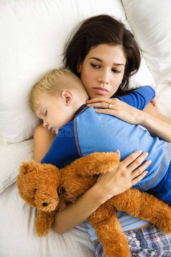 Mom with sleeping child. Caucasian mid adult woman holding sleeping toddler in bed stock images