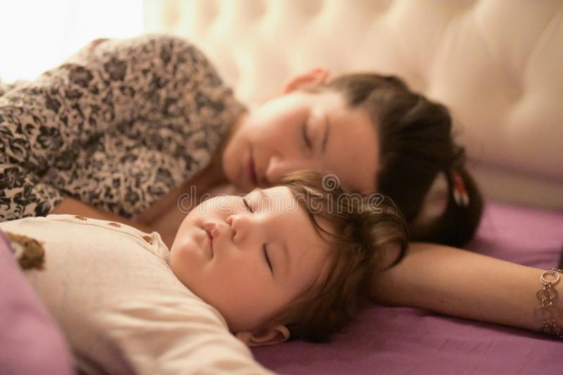 Mom is sleeping with her baby in bed. view from above. purple bed. Young mom and her cute little baby sleeping in bed together, stock image