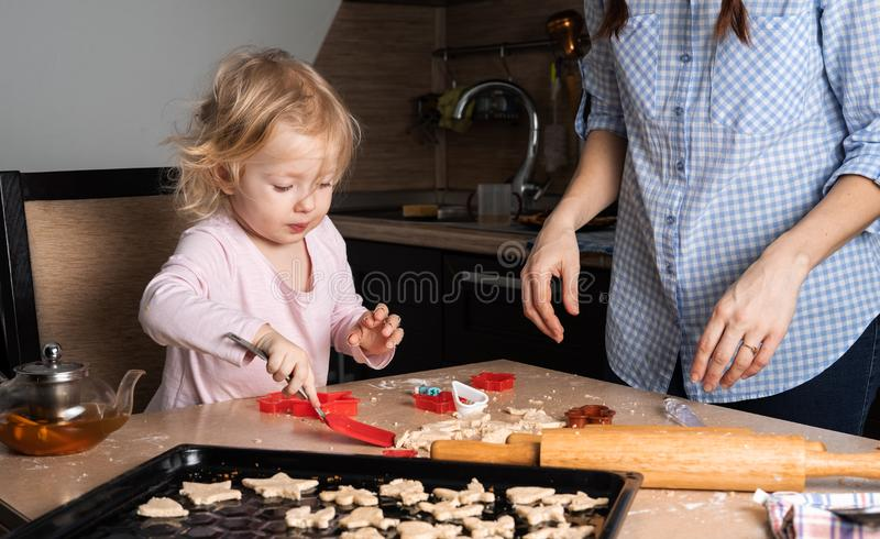 Mom with a small daughter baby is preparing cookies in the kitchen. Scene from the real life of the family. stock image