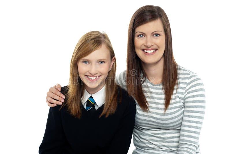 Mom som poserar med armar runt om henne den gulliga dottern arkivbilder