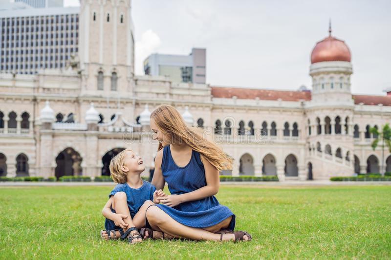 Mom and son on background of Merdeka square and Sultan Abdul Samad Building. Traveling with children concept stock photos
