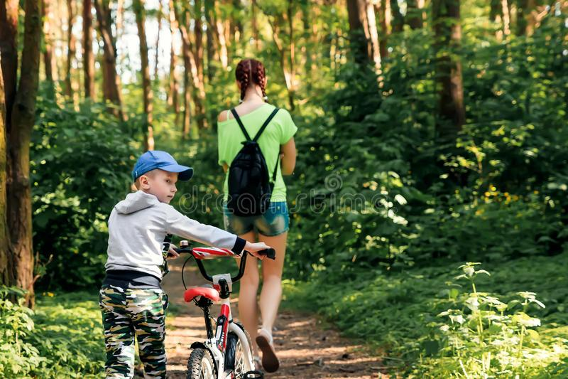 Mom and son with a bicycle stroll through the park, walk in the park opy space for text.  stock photos