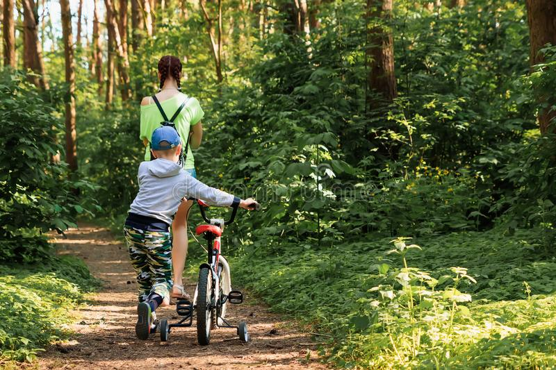 Mom and son with a bicycle stroll through the park, walk in the park opy space for text.  stock photo