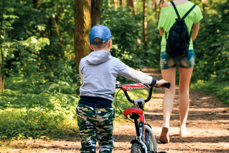 Mom and son with a bicycle stroll through the park, walk in the park.  royalty free stock photo
