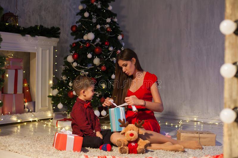 Mom and son at the Christmas tree with gifts of new year decor winter royalty free stock images