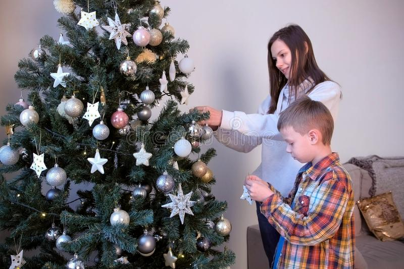 Mom and son decorating artificial Christmas tree in living room at home together. royalty free stock photo