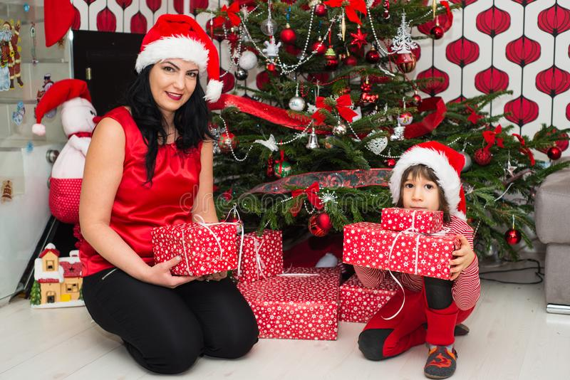 Mom and son holding presents. Mother and son in front of Xmas tree holding presents and posing together stock images